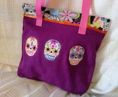 "$15.00 #CottonCanvasFabric #LargeInsidePockets #appliqued #SecureClosure #MediumToteBag For the Hip Mom "" Day of the Dead"" Medium Tote Bag This cute bag makes a great ""everything"" tote bag-- take it shopping, the farmers market, anywhere at all.  Make from 100% cotton and unlined, hand-dyed a deep purple by yours truly with design highlights from a great fabric I recently purchased. Inside is a nice large pocket to fit your cell phone, eye glasses or car keys. It is secured by a zippered…"