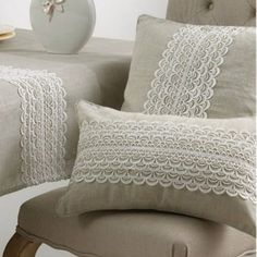 A lacy woven wave panel stretches across the width of these subtle pillows adding a little visual texture and femininity to their placement.