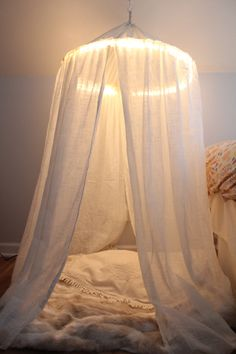 diy kids play tent. Use a hula hoop, wrap Christmas lights around it and secure it together with a sheer certain and there you have it!