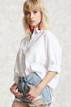 An oversized poplin shirt featuring a buttoned placket, basic collar, chest patch pocket, dropped shoulders, cuffed long sleeves, and a curved hem.