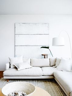 """Oversize sofas, a banquet-size dining table and a massive architectural plan cabinet recast as a sideboard complement the generous, airy spaces, their ample proportions creating a dialogue with the smaller furnishings and accessories. """"Texture also comes from the interplay of large and small pieces,"""" says Hare. In the family room a custom sofa from Fanuli, 'Oxo' coffee table from Mark Tuckey, Foscarini 'Twiggy' floor lamp by Marc Sadler from Space Furniture..."""