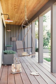 HGTV features a contemporary country gray front porch with a wood plank ceiling, outdoor red barn light sconces and a modern metal swing with rope cable.