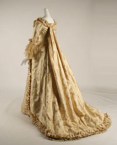 Reception gown (or costume), Mme Ed. E. Thomé, ca. 1880; silk    Metropolitan Museum of Art 1998.271a, b; Gift of Richard Martin    Victorian fashion always contained some kind of historicizing element, and in the 1880s fashion's focus was on the eighteenth century. The pleats on the back of this dress are reminiscent of the sack back of a robe à la française, as are the lacy engageants; the pleated trim is a replica of that found on many historical gowns; and the compère front, with the…
