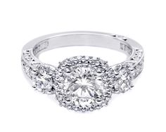 HT 2524 CU 6.5 This blooming beauty features three stones with triple the diamonds for a glamorous yet elegant Engagement Ring. Double halos of pave-set diamonds bloom each of the diamonds with the classic Tacori crescent creating sizzle on the profile.