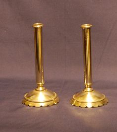 """A rare pair of George I period Brass Taper Sticks with drip pans above circular columns raised on conical petal bases. Very cute and just 6"""" tall! Circa. 1720."""
