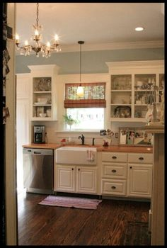 Pretty blue wall color contrasts with off-white cabinetry. Wood counter top and natural window shade provides warmth.