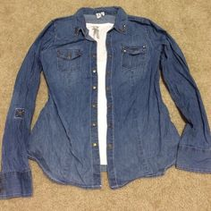 Studded denim button-down shirt Medium denim shirt from Marshals with metal accents. Includes the fabric and button to keep sleeve rolled up. Worn once or twice but no damage. The buttons on the front are snaps. No trades thanks! Tops Button Down Shirts