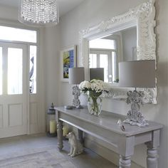 Love the sort grays of this entry hall. The formal mirror painted a shiny white is great.