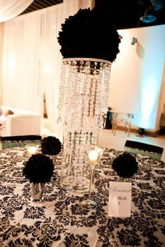 Black flower ball in giant cylinder vase with chandelier. reception wedding flowers, wedding decor, wedding flower centerpiece, wedding flower arrangement, add pic source on comment and we will update it. www.myfloweraffair.com can create this beautiful wedding flower look.