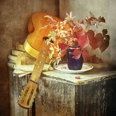 http://pixels.com/products/guitar-and-blue-vase-nikolay-panov-art-print.html Floral still life photography with old guitar and bouquet of yellow and red autumn leaves in deep blue vase on beige rustic table in interior lighted by bright sun in fall season