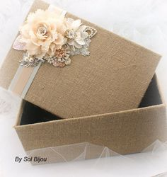 ****Ready to Ship ***This listing is for a shabby-chic burlap keepsake box as shown or in any color combination This delectable keepsake box has been created with burlap. Crafted to perfection, this memory box has been decorated with my luscious handmade flowers, pearls and a pretty crystal and pearl brooch. Champagne, Ivory and Blush tones can be seen in this heirloom piece. This rustic, yet chic box makes a gorgeous decor piece for your home. Thes habby-chic box accessory is ideal to…