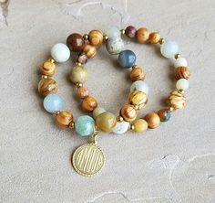 "Earth tone agate, gold hematite, wood beads and brass amour charm. Bracelet is approximately 7"". Looks great with our Earth Tone Agate Olive Bullet Shell Tassel which is sold separately."