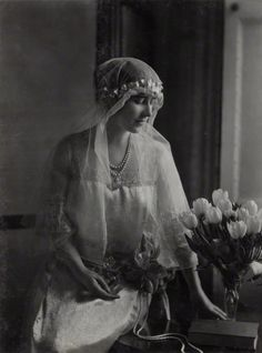 Photo by Lafayette in 1922 of Queen Elizabeth (Elizabeth Angela Marguerite) (nee Bowes Lyon) Windsor (4 Aug 1900 UK-30 Mar 2002 UK age 101) Scotland sitting in bridal dress for Princess Mary's wedding (1897-1965) UK to Henry Lascelles (1882-1947) 6th Earl of Harewood, UK, looking down at flowers. Elizabeth is the Future Wife 1923 of King George VI (Albert Frederick Arthur George Windsor) (14 Dec 1895 UK–6 Feb 1952 UK age 56) UK. Located 2016 UK National Portrait Collection NPG Ax29335.