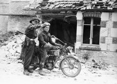 A Canadian despatch rider on a Norton 16H getting directions in a Normandy village/June 1944