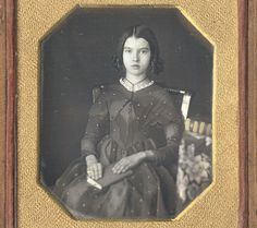 "Sixth plate daguerreotype showing a sweet young girl with book, anonymous American circa 1845. Housed in a full leather case with repaired spine, inverted ""Wm. Shew / Miniature Case Maker"" label in interior"