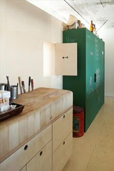 Plywood cupboard doors - like holes for handles.  The green, red and off white look good together.