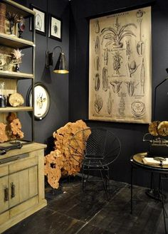 "Against a dark background, wall art that would  normally blend in becomes a focal point. Antiques and naturalistic accessories (like the fossilized rocks and botanical wall hanging here) look more modern against black paint and stop the ""living in a museum"" feel in its tracks."