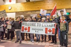 More than 30 people from Osoyoos and other communities came to the airport in Penticton to welcome the arrival of a Syrian Refugee family, the Tabanjats, who have been sponsored to come to Osoyoos. They brought signs and banners in English and Arabic welcoming the family. The family was overwhelmed and kept expressing thanks. (Richard McGuire photo)