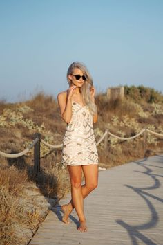 On Formentera Island wearing a sequin Sailor dress from Revolve clothing and ray ban clubmasters in black with white hair and a beautiful background