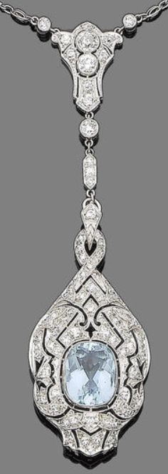 A belle époque aquamarine and diamond pendant necklace, circa 1905.  The finely pierced plaque with foliate and scrolling detail, millegrain-set throughout with single-cut diamonds, and set to the centre with a cushion-shaped aquamarine, suspended from an old brilliant-cut diamond triangular-shaped surmount, to a fancy-link chain, interspersed to the front with trios of similarly-cut diamonds in hexagonal collet-settings, diamonds approx. 2.35cts total. Via Bonhams.