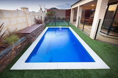 The Portofino Fiberglass Pool is set against grass. It is long enough for a lap pool. The placement of the seats for this Florentina faces the house, making it the perfect for setting for a weekend boxing fight or football game.