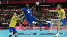 Luc Abalo of France jumps to shoot while Dalibor Doder (L) and Jonas Larholm (R) of Sweden can just watch on during the men's Handball preliminaries group A match between France and Sweden on Day 10 of the London 2012 Olympic Games at the Copper Box.
