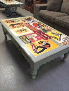 Unieke krijtverf meubelen. Salontafel in de concrete grey met inleg van oude reclameposters. Let op de gouden franje langs de zijregels en laden.