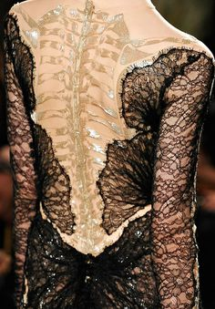 Marchesa, Fall 2012 Tulle body suit with a gold embroidered skeleton, worn underneath a black lace dress.