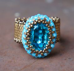 This ring is made with a 13x18mm Swarovski Turquoise crystal cabochon. It is beaded with 11/0 Turquoise Alabaster Seed Beads, 11/0 Bronze Delica, and 15/0 Bronze Seed Beads.