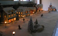 Christmas village finished shows front of church, boulders surrounded by pine trees, street lampposts and people