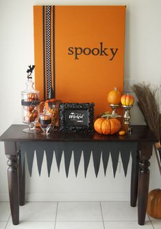 fun and easy halloween sign/decoration for table - just cover a canvas with orange fabric, add some black ribbon, and paint or add stickers of a halloween saying like spooky, boo, or trick-or-treat.