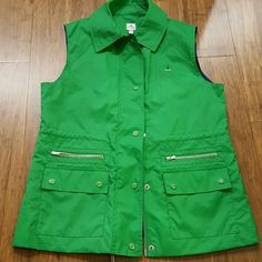Peter Millar golf vest NWOT green vest with four pockets, zip closure, and inner drawstring. Comes with extra snap. Outer 100% nylon, lining 100% polyester. Logo on left chest is a small palm tree. Measures approx 18.25 inches armpit to armpit zipped and 25 shoulder to hem. No trades or PayPal. Offers welcome. Peter Millar Jackets & Coats Vests