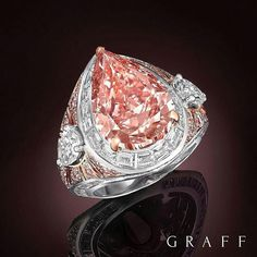 A dramatic setting of radiating white and pink diamonds, a rare and stunning 8.97 carat pear shape Fancy Vivid Pink diamond takes centre stage.