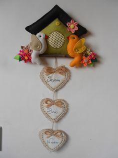 Trabalho em feltro colorido, tecido e juta, recheado com fibra siliconada. Casinha, dois pássaros e flores sobre um galho de eucalipto e 3 corações com a inscrição Sejam Bem Vindos (opcional). Pode ser feito em qualquer tema.