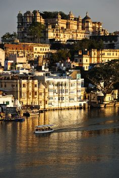 Last bit of sunlight illuminates the town of Udaipur, with Udaipur Palace at the top. India.