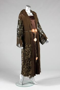 * Paul Poiret dinner gown, circa 1918-20, labelled 'Paul Poiret a Paris, Joseph New York' with Iribe rose to the waist area, comprising chemise-like under-dress of brown satin, with girdle of gold tape with ribbon roses, integral brown silk filet lace coat with knotted chiffon collar