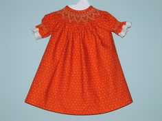 Orange bishop dress for American Girl doll with gold/tan smocking and white eyelet trim on the sleeves.