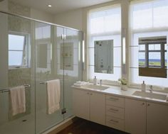 modern white tile, towel bars on glass doors, large nook in shower, floating mirrors on windows- cool