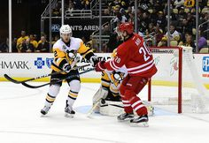 Sebastian Aho Photos Photos - Chad Ruhwedel #2 of the Pittsburgh Penguins and Sebastian Aho #20 the Carolina Hurricanes reach for the puck at PPG PAINTS Arena on December 28, 2016 in Pittsburgh, Pennsylvania. - Carolina Hurricanes v Pittsburgh Penguins