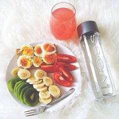 Delicious breakfast: banana, kiwi, tomatoes, toast and egg , with water and grapefruit juice.