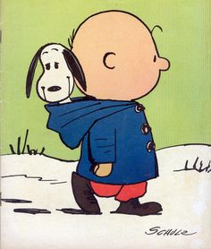 Charlie Brown carrying Snoopy through the snow, giving a twist to the phrase 'hood ornament'.