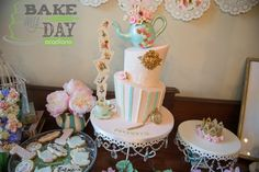 Topsy turvy vintage One-derland themed tea party cake. Teapot is modeling chocolate, pocket watch is gumpaste and a poured isomalt face. Cards are gumpaste with edible images, and shaped together with isomalt. Teapot and saucer are gumpaste.