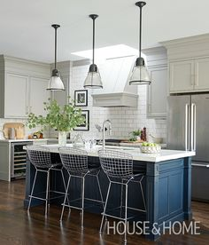 A midnight blue island with ornate moldings was the sole piece designer Rachel Fox salvaged from this family's original kitchen. | Photographer: Alex Lukey