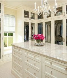 Feminine walk in closet featuring a white dresser with silver hardware, chandelier, and pink flowers.  (Dislike the closet doors.)