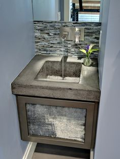 The hardware is really cool and the concrete countertop is a brilliant choice for this vanity cabinet!