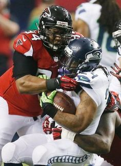 Seattle Seahawks running back Marshawn Lynch (24) is hit by Atlanta Falcons defensive tackle Peria Jerry (94) and Atlanta Falcons defensive tackle Jonathan Babineaux, right, during the first half of an NFC divisional playoff NFL football game Sunday, Jan. 13, 2013, in Atlanta. (AP Photo/John Bazemore)