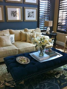 Lovely tufted blue velvet ottoman as a coffee table alternative! Gorgeous blue floral rug. Super comfy-looking couch with embroidered accent pillows. Fresh flowers. And finally the wood shutters...all add to the homey, comfortable, welcoming feeling!