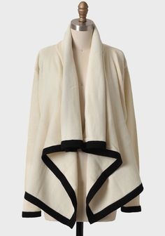 This knit open cardigan in cream features a contrasting black trim and an asymmetrical cut to add movement to any outfit.