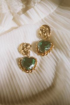 Vintage Rare Moschino Cherub Earrings Features Gold Tone Cherubs, Green Glass Hearts, and Rope Base Detailing Clip on Detail Measurements: Length - *Light Wear to Gold Tone and to Color in Glass Heart - Still Beautiful Condition Ear Jewelry, Cute Jewelry, Gold Jewelry, Jewelry Box, Jewelry Accessories, Fashion Accessories, Fashion Jewelry, Jewlery, Gold Earrings