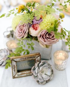 Arrangements of roses, zinnias, chamomile, ferns, zinnias, and scabiosa were surrounded by mercury glass votive candleholders, loose succulents, and framed calligraphed table numbers.